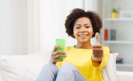 Mujer africana feliz con smartphone en casa Fotografía de archivo libre de regalías