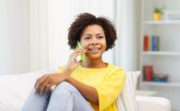 Mujer africana feliz con smartphone en casa Foto de archivo