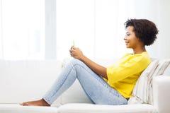 Mujer africana feliz con smartphone en casa Imagen de archivo libre de regalías