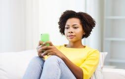Mujer africana feliz con smartphone en casa Imagen de archivo