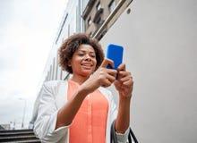 Mujer africana feliz con smartphone en ciudad Fotos de archivo libres de regalías