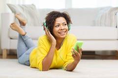 Mujer africana feliz con smartphone y los auriculares Fotos de archivo
