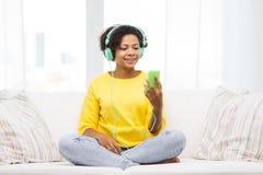 Mujer africana feliz con smartphone y los auriculares Imagen de archivo libre de regalías
