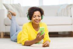 Mujer africana feliz con smartphone y los auriculares Fotos de archivo libres de regalías