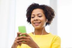 Mujer africana feliz con smartphone y los auriculares Foto de archivo libre de regalías