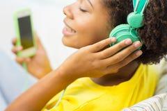 Mujer africana feliz con smartphone y los auriculares Fotografía de archivo libre de regalías