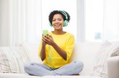 Mujer africana feliz con smartphone y los auriculares Fotografía de archivo