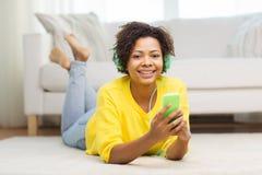 Mujer africana feliz con smartphone y los auriculares Foto de archivo