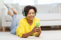 Mujer africana feliz con smartphone y los auriculares Imagenes de archivo