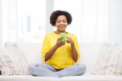 Mujer africana feliz con smartphone y los auriculares Imagen de archivo