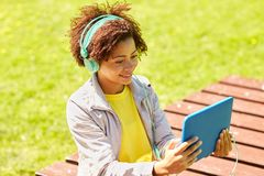 Mujer africana feliz en auriculares con PC de la tableta Imágenes de archivo libres de regalías