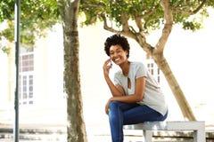 Mujer africana feliz en un banco usando el teléfono móvil Fotos de archivo