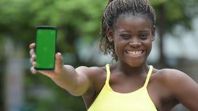 Mujer africana feliz joven que muestra el teléfono al aire libre almacen de video
