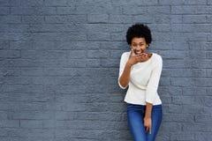 Mujer africana feliz que cubre su boca y risa imagenes de archivo
