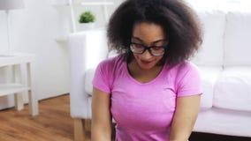 Mujer africana feliz que ejercita en la estera en casa almacen de video