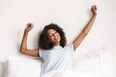 Mujer africana feliz que estira sus manos mientras que se sienta en cama imagen de archivo