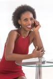 mujer africana feliz que habla en su teléfono celular y sonrisa Foto de archivo