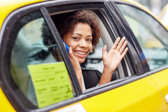 Mujer africana feliz que invita a smartphone en taxi foto de archivo libre de regalías