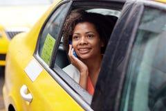Mujer africana feliz que invita a smartphone en taxi Imagen de archivo libre de regalías