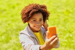 Mujer africana feliz que toma el selfie con smartphone Foto de archivo libre de regalías