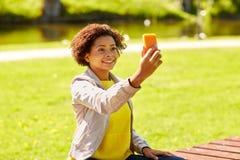 Mujer africana feliz que toma el selfie con smartphone Imagenes de archivo