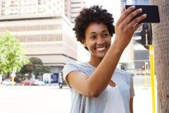 Mujer africana feliz que toma un selfie Imagenes de archivo