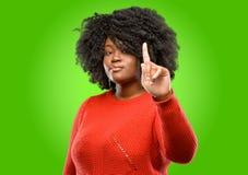 Mujer africana hermosa con el pelo rizado aislado sobre fondo verde fotografía de archivo