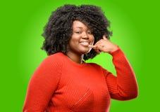 Mujer africana hermosa con el pelo rizado aislado sobre fondo verde imagenes de archivo