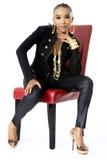 Mujer africana hermosa joven que se sienta en silla roja Fotografía de archivo