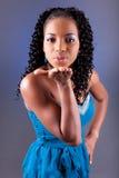 Mujer africana hermosa joven que sopla un beso Imagen de archivo libre de regalías