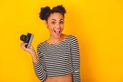 Mujer africana joven aislada en el estilo adolescente del estudio amarillo de la pared que sostiene la cámara Fotografía de archivo libre de regalías