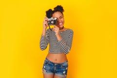Mujer africana joven aislada en el estilo adolescente del estudio amarillo de la pared que toma las fotos Imagen de archivo