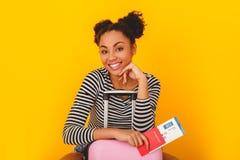 Mujer africana joven aislada en el viajero adolescente del estilo del estudio amarillo de la pared que se sienta en la maleta Imagen de archivo