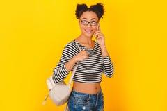 Mujer africana joven aislada en estilo adolescente del estudio amarillo de la pared con llamada de teléfono de la mochila Imágenes de archivo libres de regalías
