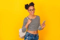 Mujer africana joven aislada en estilo adolescente del estudio amarillo de la pared con la mochila que sostiene smartphone Imagen de archivo