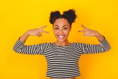 Mujer africana joven aislada en la diversión adolescente del estilo del estudio amarillo de la pared Fotografía de archivo libre de regalías