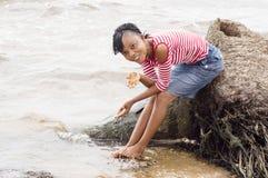 Mujer africana joven al borde de la laguna Imagenes de archivo