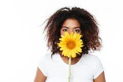 Mujer africana joven alegre que sostiene la flor Foto de archivo libre de regalías