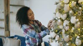 Mujer africana joven atractiva que adorna el árbol de navidad en casa que se prepara para la celebración de Navidad almacen de video
