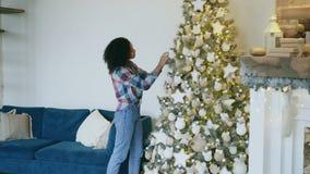 Mujer africana joven atractiva que adorna el árbol de navidad en casa que se prepara para la celebración de Navidad metrajes