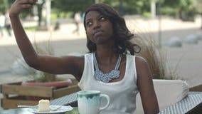 Mujer africana joven atractiva que sonríe y que toma un selfie con su smartphone mientras que se sienta solamente en café al aire metrajes