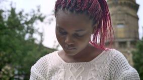 Mujer africana joven con el libro de lectura rosado de los dreadlocks y sentada en banco en parque cerca de la universidad almacen de video