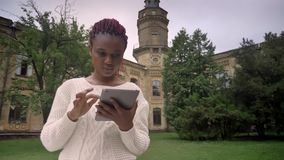 Mujer africana joven con los dreadlocks rosados en el suéter blanco que mecanografía en la tableta, sentándose en parque cerca de metrajes