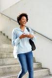 Mujer africana joven de risa que camina abajo de los pasos Fotografía de archivo
