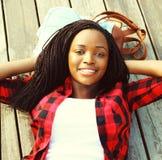 Mujer africana joven del retrato relajada en un piso de madera con las manos detrás de la cabeza, llevando una camisa a cuadros r Imagen de archivo