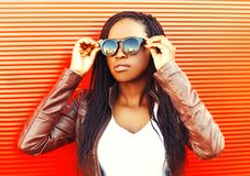 Mujer africana joven elegante que lleva una chaqueta, gafas de sol en ciudad imagenes de archivo