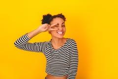 Mujer africana joven en la presentación adolescente del estilo del estudio amarillo de la pared Foto de archivo libre de regalías