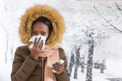 Mujer africana joven enferma del retrato del primer con la capa encapuchada con la piel, fondo del invierno de la nariz que sopla Imagen de archivo libre de regalías