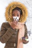 Mujer africana joven enferma del retrato del primer con la capa encapuchada con la piel, fondo del invierno de la nariz que sopla Fotos de archivo libres de regalías