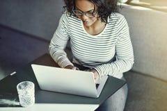 Mujer africana joven enfocada que trabaja en línea con un ordenador portátil fotografía de archivo libre de regalías